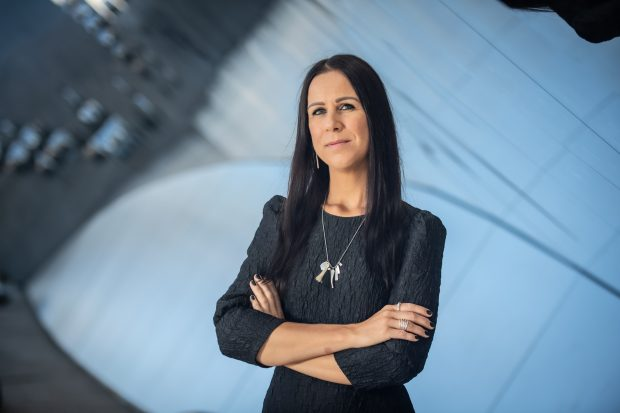 Photograph of a woman with long dark hair in a black dress with her arms folded, against an abstract background.