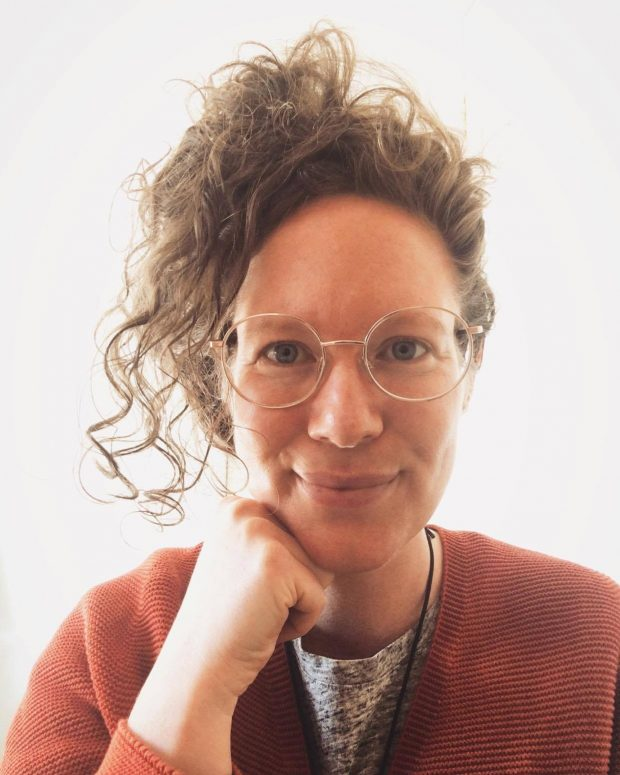 Photo of white female with glasses and curly hair.